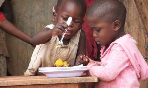 Ugandan children dig in to a plate of orange sweet potato.