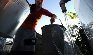Woman collecting water from community pump in rural Azerbaijan.