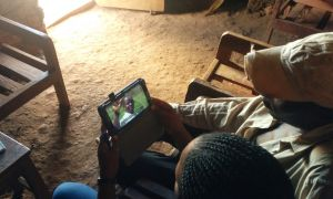 A farmer is being shown a video on PSS at his home (photo credit Charles Wanume)