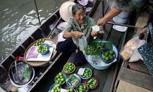 A woman trades her produce in a floating market in Bangkok, Thailand.