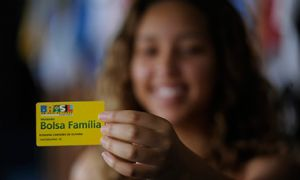 Woman, blurred in background, holds up Bolsa Família card, sharp in foreground