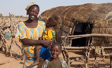 Mother and children outside of thatched hut in Northern Senegal.