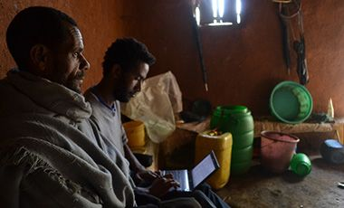 Two men in hut, one researcher with laptop.