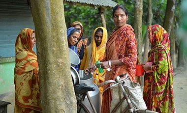 A woman milk collector collecting morning milk form women dairy farmers in Bangladesh