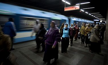 Women exit Sadat tube station on a platform as a train travels past.