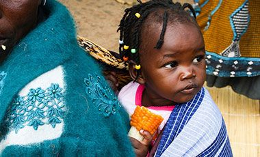 Very young girl in Zambia eating vitamin A maize