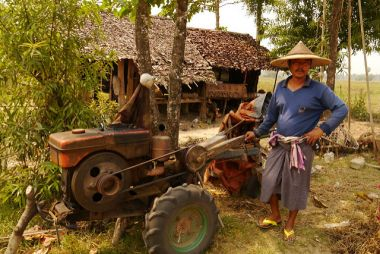 Farmer in Myanmar Poses Next to his Tractor