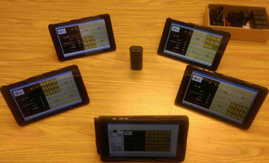 Several devices displaying the noncropshare game are displayed on a table