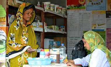 A female livestock health worker prescribing drugs for a woman diary farmer in Bangladesh