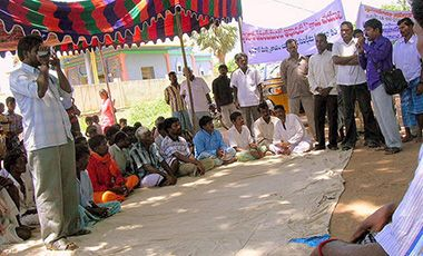 Men sitting and standing in a circle outdoors - Community meeting in Andhra Pradesh