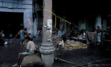 People sitting, lying down, along street in India.