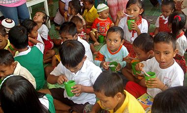 Group of Indonesian children eating out of cups